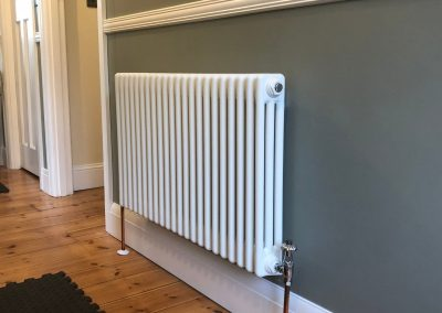 Heating and plumbing gallery - new radiator installed on a grey wall - Freeflow heating and plumbing