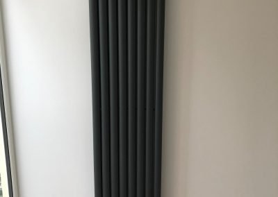Heating and plumbing gallery - new tall radiator installed on a white wall - Freeflow heating and plumbing