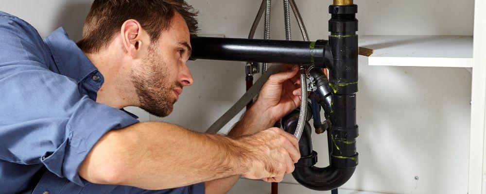 Plumbing Plymouth - plumber fixing sink - Freeflow Plumbing and Heating